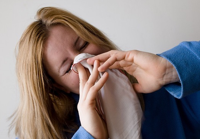 Woman with a cold blowing nose