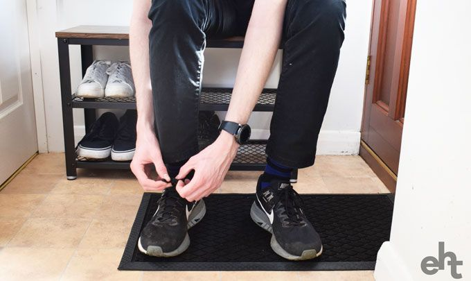 man tying shoelaces sat on a shoe storage bench
